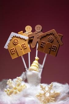 Huizen en mensen van zwarte en melkchocolade op een stokje