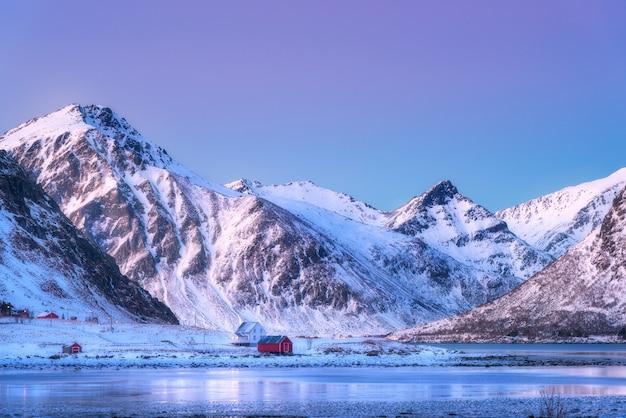 Huizen en prachtige sneeuw bedekte bergen in de winter in de schemering