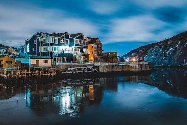 Huizen in de buurt van waterlichaam tijdens de nacht