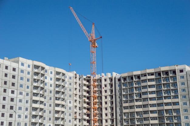 Huizen met meerdere verdiepingen in aanbouw en hoogbouwkranen