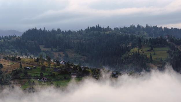 Huizen op de karpaten berg piek boven de wolken in mistige ochtend