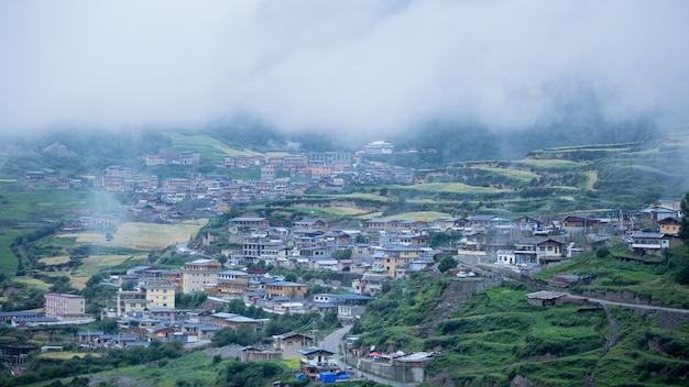 Huizen van een kleine stad omgeven door bossen en een mistige wolk