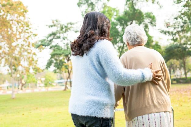 Hulp en zorg aziatische senior vrouw gebruik rollator in het park.