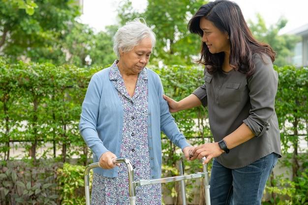 Hulp en zorg aziatische senior vrouw gebruik rollator in park.