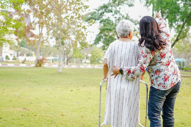 Hulp en zorg aziatische senior vrouw gebruik walker in park.