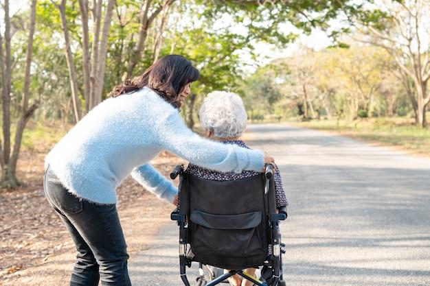 Hulp en zorg aziatische senior vrouw patiënt op rolstoel in park.