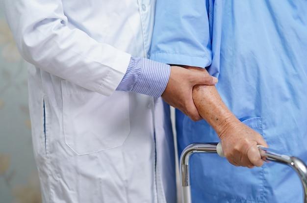 Hulp en zorg van de arts aziatische senior vrouw gebruik walker.