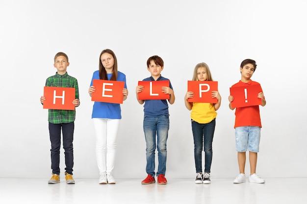 Hulp verwarmt het hart. groep droevige ernstige kinderen of tieners die met rode banners woord maken dat op studioachtergrond wordt geïsoleerd. onderwijs, reclame en sociale rechten concept. familie problemen concepten.