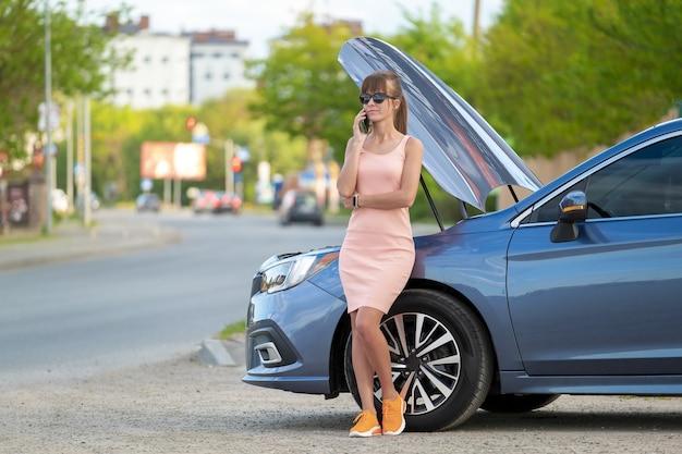 Hulpeloze vrouw die in de buurt van de auto staat met een open kap die op de mobiele telefoon belt voor hulp.
