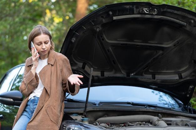 Hulpeloze vrouwenchauffeur die om hulp / assistentie roept die naar defecte auto kijkt, stopte langs de weg.