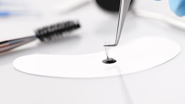 Hulpmiddelen en accessoires voor de procedure voor het verlengen van de wimpers. valse wimper en druppel wimperlijm.