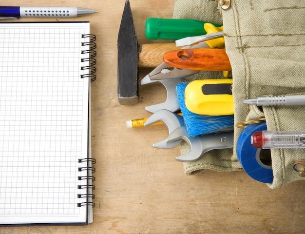 Hulpmiddelen en notitieboekje op houtstructuur