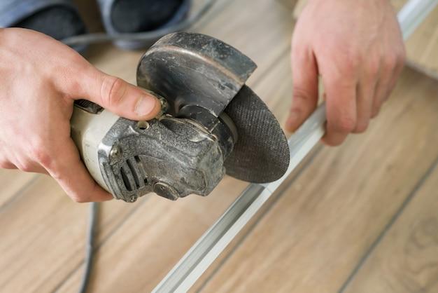 Hulpmiddelen om tegel te snijden, mannetje die snijder met behulp van