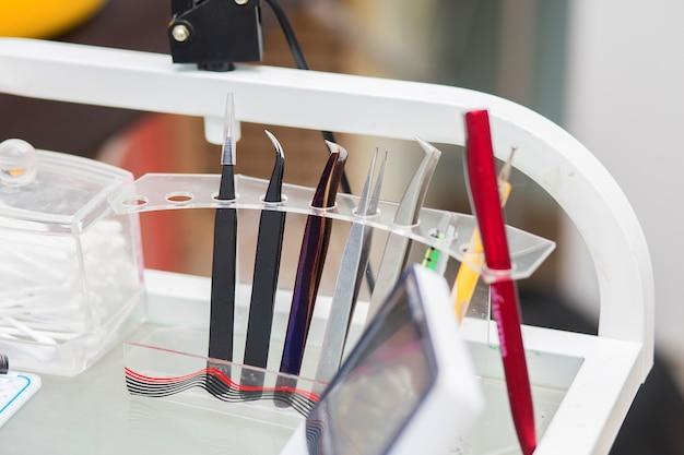 Hulpmiddelen van de meester in wimperuitbreidingssteun in een steun op een desktop, in schoonheidswinkel