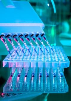 Hulpmiddelen voor dna-analyse, pcr-meerkanaalspipet en plaat met 96 putjes, testen van coronavirus-nucleïnezuren wordt uitgevoerd. nieuw coronavirus covid-19 testen op nucleïnezuren, signatuur van sars-cov-2.