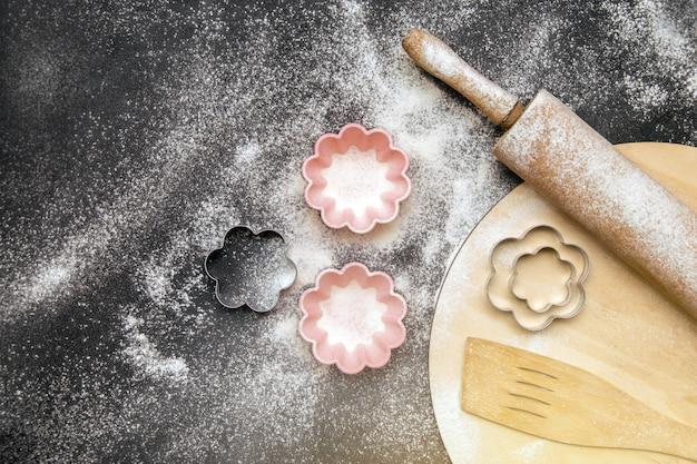 Hulpmiddelen voor het bakken op een zwarte achtergrond met met bloem bestoven bloem
