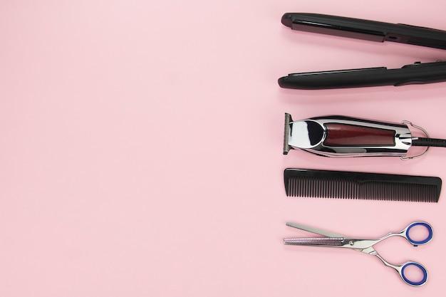 Hulpmiddelen voor het knippen en stylen van haar op een roze achtergrond