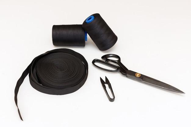 Hulpmiddelen voor het naaien op een homogene achtergrond. schaar, draden en tape. handwerken en hobby's