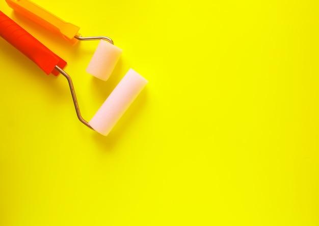 Hulpmiddelen voor huisreparatie op felgele achtergrond. twee schuimrollers voor muurkleuring close-up.