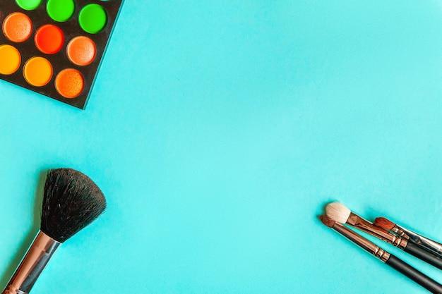 Hulpmiddelen voor make-up en cosmetica verschillende tinten oogschaduw palet en make-up kwast op trendy kleurrijke blauwe pasteltafel. bovenaanzicht plat lag