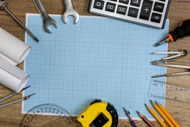 Hulpmiddelen voor tekenen met millimeterpapier op houten achtergrond