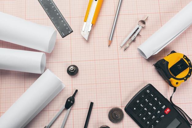 Hulpmiddelen voor tekenen op rood millimeterpapier met kopie ruimte