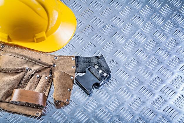 Hulpmiddelriem de bouwhelm op het gegroefde bouwconcept van de metaalplaat