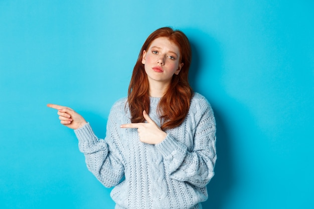 Humeurig tienermeisje met rood haar, wijzende vingers naar links naar logo, staren gehinderd en verveeld, staande over blauwe achtergrond.