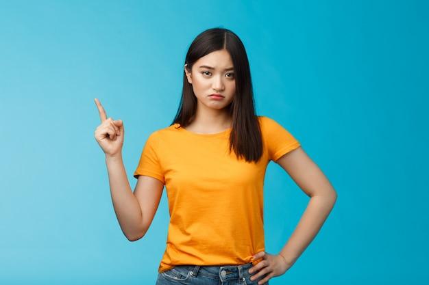 Humeurige overstuur aziatische vriendin, mokkende blik beledigd en ontevreden wijzend naar de linkerbovenhoek, teleurgesteld pruilend, staande verontruste blauwe achtergrond dragen geel t-shirt. ruimte kopiëren