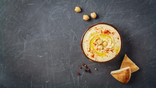 Hummus bord met pita plat brood, kikkererwten en kruiden. bovenaanzicht, kopie ruimte.