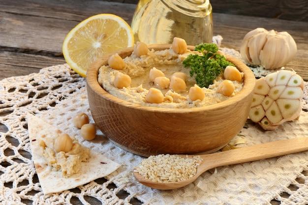 Hummus in een houten kom en ingrediënten om het op tafel te koken