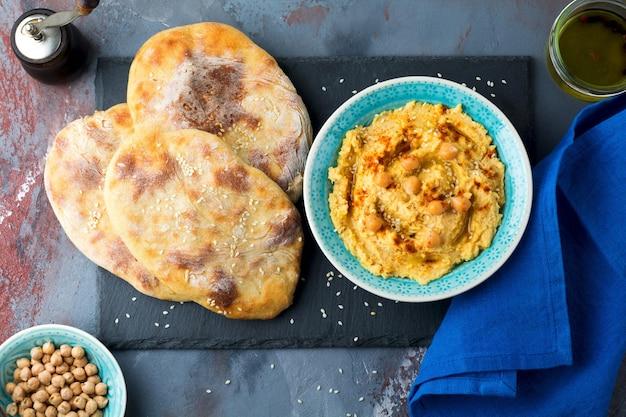 Hummus, kikkererwten, met kruiden en pitabroodje, platte cake in een bord op een oppervlak van grijze steen