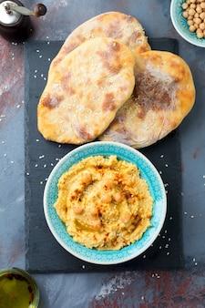Hummus, kikkererwten, met kruiden en pitabroodje, platte cake in een plaat op een achtergrond van grijze steen. selectieve aandacht.