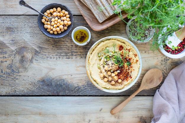 Hummus, kikkererwtensaus met gerookte paprika olijfolie in een keramische kom op een houten achtergrond. bovenaanzicht. kopieer ruimte.