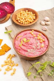 Hummus met bieten en microgreen basilicumspruiten in houten kom op een witte houten lijst en linnentextiel. zijaanzicht, close-up.