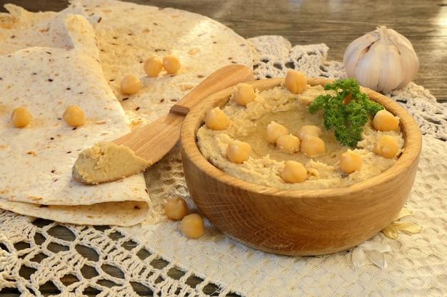 Hummus met pitabroodje en knoflook op een houten tafel