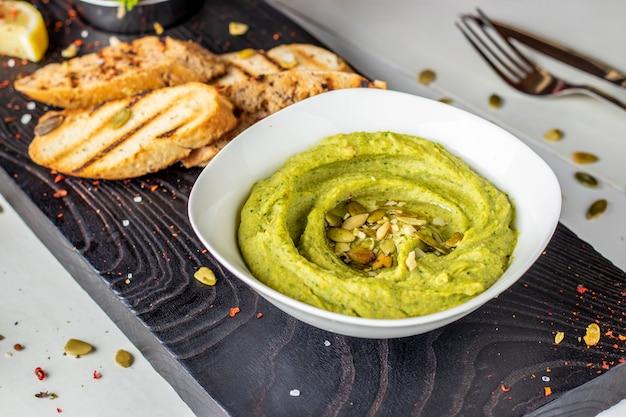 Hummus met spinazie en pompoenzaden in een kom op een houten raad en bruschetta, oosterse keuken, horizontale foto