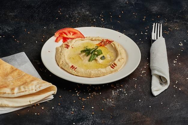 Hummus van kikkererwten op donkere achtergrond. midden-oosterse, joodse keuken of arabische gerechten. veganistisch, vegetarisch voedselconcept.