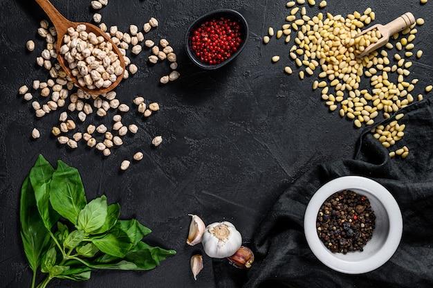 Hummusingrediënten, knoflook, kikkererwten, pijnboompitten, basilicum, peper. zwarte achtergrond. bovenaanzicht ruimte voor tekst.
