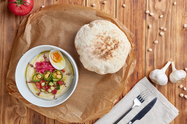 Hummuskom met pitabroodje, pitabroodje, houten achtergrond