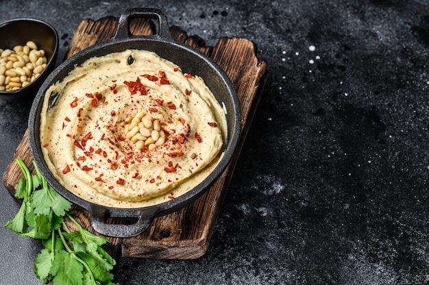 Hummuspasta met kikkererwten en peterselie in een kom. zwarte achtergrond. bovenaanzicht. ruimte kopiëren.