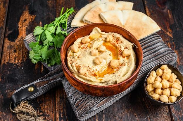 Hummuspasta met pitabroodje, kikkererwten en peterselie in een houten kom. donkere houten achtergrond. bovenaanzicht.