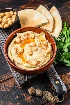 Hummuspasta met pitabroodje, kikkererwten en peterselie in een houten kom.
