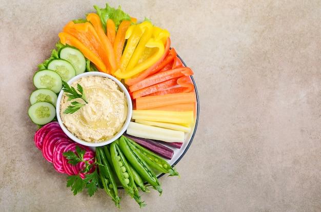 Hummusschotel met diverse groentesnacks. gezond veganistisch en vegetarisch eten. bovenaanzicht, plat lag, kopie ruimte.