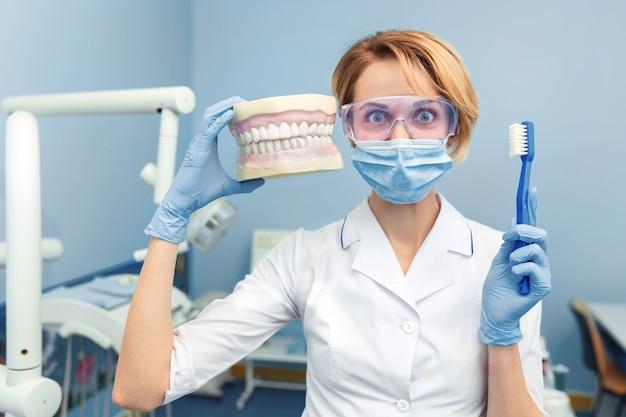 Humor. tandarts die een menselijke kaak en een tandenborstel in hand houdt. grappige emotie