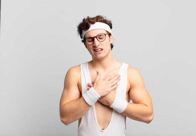 Humoristische sportman die er verdrietig, gekwetst en diepbedroefd uitziet, beide handen dicht bij het hart houdt, huilt en zich depressief voelt