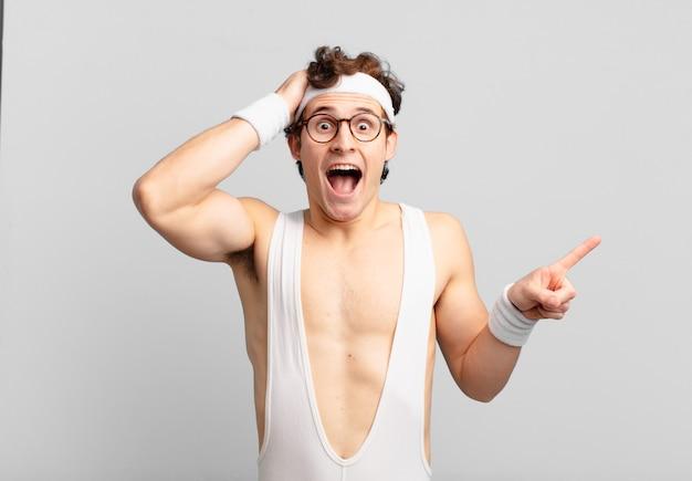 Humoristische sportman die lacht, er blij, positief en verrast uitziet en een geweldig idee realiseert dat naar de laterale kopieerruimte wijst