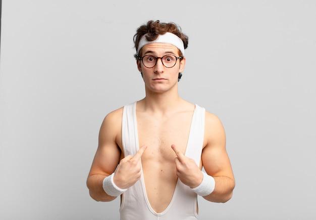 Humoristische sportman die naar zichzelf wijst met een verwarde en vragende blik, geschokt en verrast om gekozen te worden