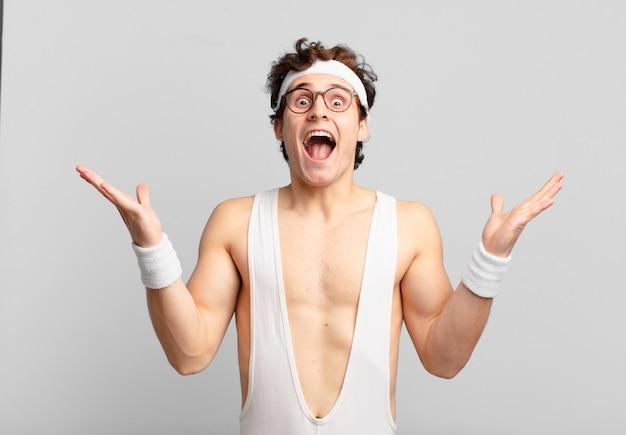 Humoristische sportman die zich gelukkig, verbaasd, gelukkig en verrast voelt en de overwinning viert met beide handen in de lucht