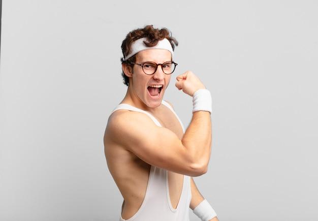 Humoristische sportman voelt zich gelukkig, tevreden en krachtig, buigt fit en gespierde biceps, ziet er sterk uit na de sportschool